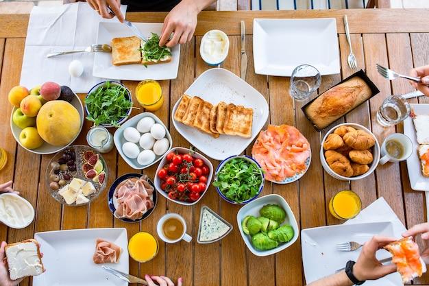 연어와 아보카도를 곁들인 토스트를 먹는 가족아침식사를 하는 가족