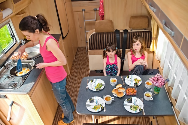 Family eating together in rv interior, mother and kids travel in motorhome on family vacation with children