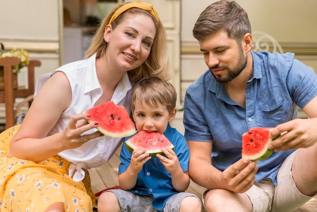 Family eating together watermelon next to a caravan
