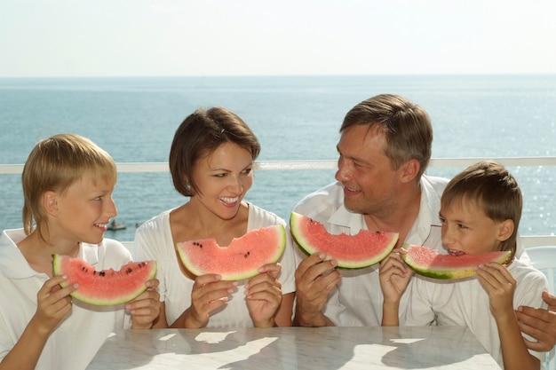 Семья ест арбуз на фоне моря