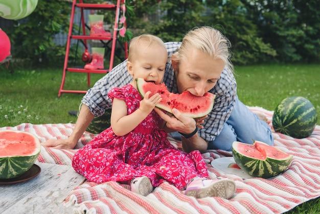 Семья ест арбуз на пикнике