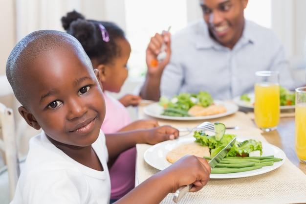 카메라를 웃는 아들과 함께 건강한 식사를 즐기는 가족