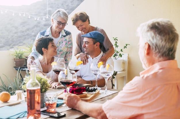 家のオープンテラスエリアで食べ物や飲み物を楽しむ家族。赤ワインと食事を楽しみながら一緒に楽しい時間を過ごす陽気な家族。テラスパーティーで話し合う愛する家族