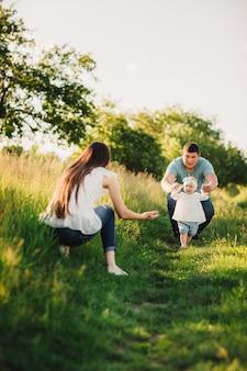 Семья наслаждается совместной жизнью в летнем парке. счастливая молодая семья на открытом воздухе.