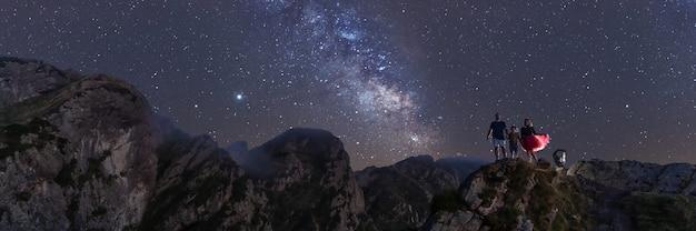 天の川の景色を望む山の頂上で夜を楽しむ家族