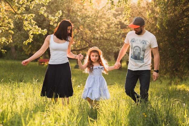 公園で緑の草の上を歩く家族を楽しむ