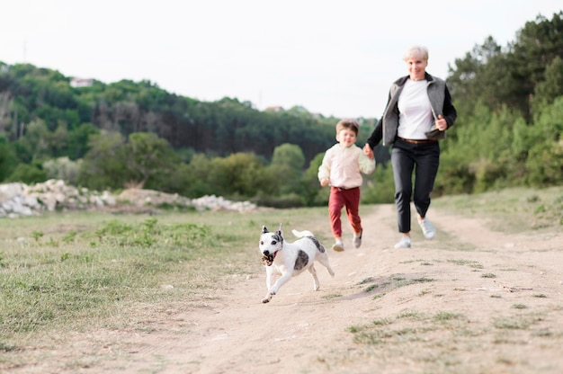 Family enjoying walk in the park with dog