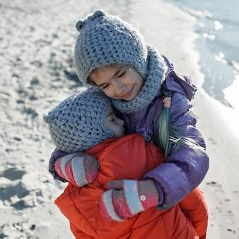 Семья наслаждается зимой вместе, дети гуляют по пляжу зимой
