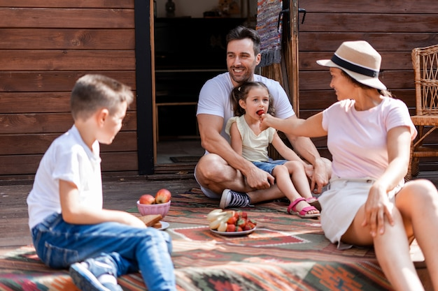 The family enjoys a quiet holiday outside the city, eats fruit on the porch of their wooden house, the mother feeds her daughter strawberries