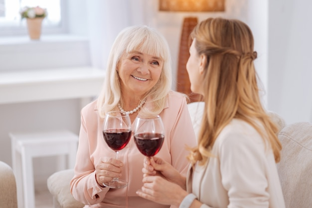 Family evening. joyful nice positive mother and daughter looking at each other and holding glasses with wine while enjoying the drink
