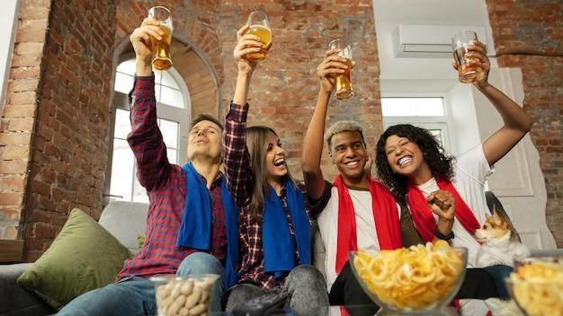 Семья. взволнованные люди смотрят спортивный матч, чемпионат дома. многонациональная группа друзей.