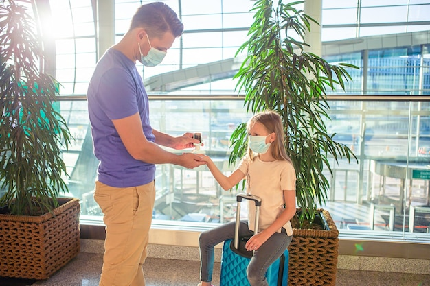 Family in face mask in airport. father and child wear facemask during coronavirus and flu outbreak. hand sanitizer in public place for virus and illness protection