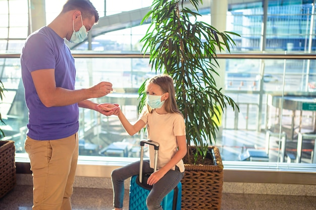 Family in face mask in airport. hand sanitizer in public place for virus and illness protection