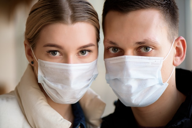 Family in face mask in shopping mall or airport. couple wear facemask during coronavirus and flu outbreak. virus and illness protection in public crowded place.