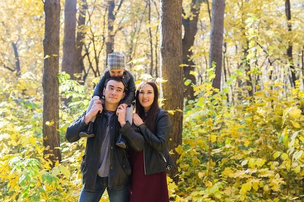 家族、秋、人々の概念-秋の日に公園を歩いて、抱き合って笑顔の若い家族。