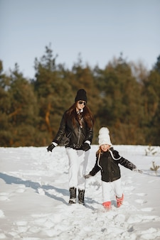 Family on family christmas vacation. woman and little girl in a forest. people walks.
