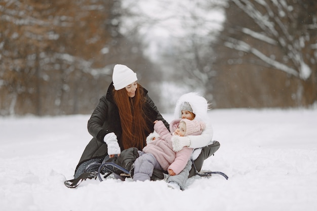Family on family christmas vacation. woman and little girl in a park. people with sled.