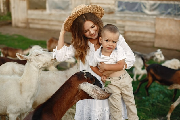 Family in a farm. people playing with a goats. mother with son.