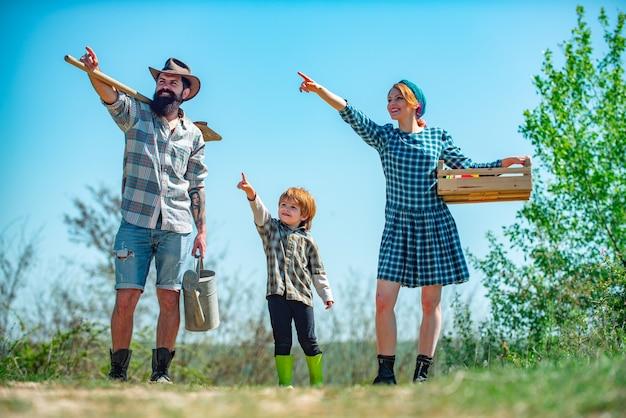 Семейные фермеры, указывающие на небо, люди, появляющиеся в саду на заднем дворе, пара с ребенком фермеров ...