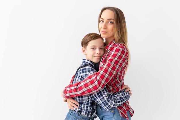 Концепция дня семьи, моды и матери - мальчик-подросток обнимает свою маму на белом фоне.