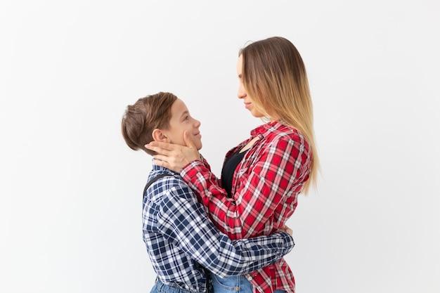 Концепция дня семьи, моды и матери - мальчик-подросток обнимает свою маму на белой стене