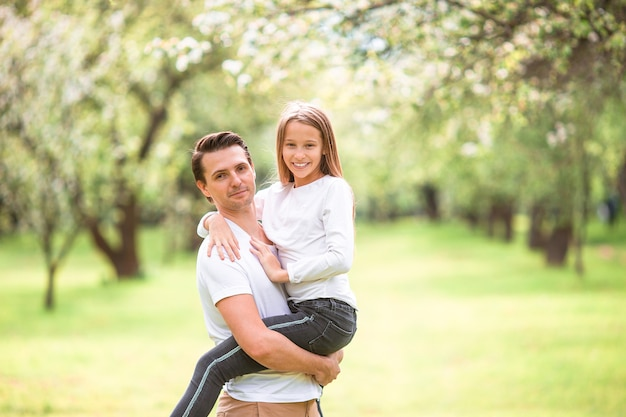 Family of father and daughter in blooming cherry garden