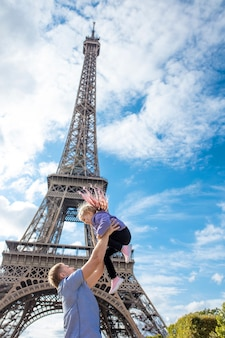 Family father and daughter happy and cheerful in paris against the background of the eiffel tower