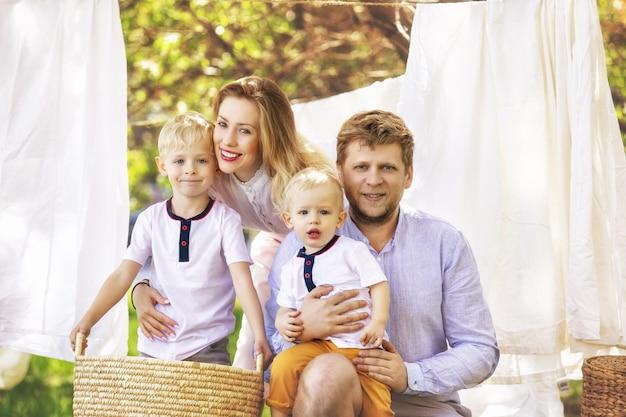 家族の父母と美しくて幸せな2人の息子が一緒に庭にきれいな洗濯物を掛けます