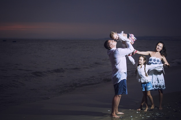 Family father mother child girl and baby on the beach against the sea and the sunset beautiful