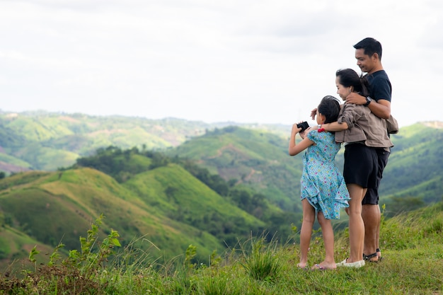 Family of father, mother and daughter taking selfie on the top of mountain
