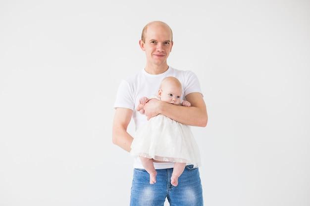 Концепция семьи, отцовства и детей - лысый отец держит симпатичного новорожденного на белой стене