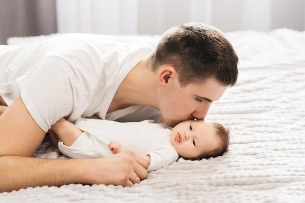 家族、父性、人々の概念-家で小さな赤ん坊の娘を抱いて幸せな父