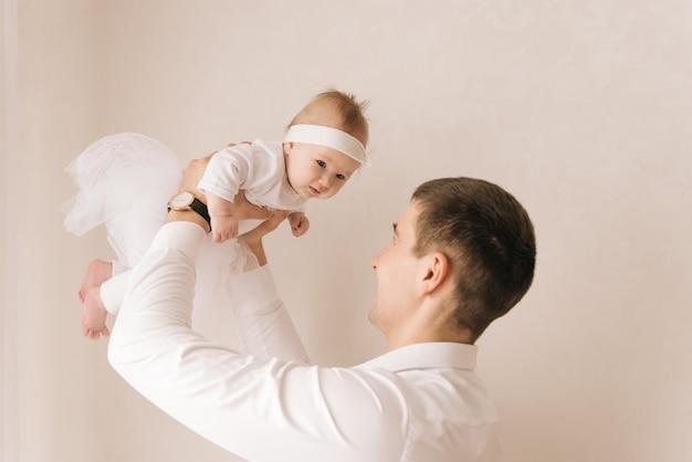 家族、父性、人々の概念-明るい背景に小さな赤ん坊の娘を抱いて幸せな父