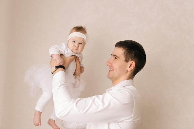 家族、父性、人々のコンセプト – 明るい背景に小さな赤ん坊の娘を持つ幸せな父親