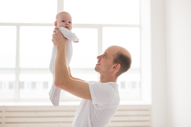 Family, fatherhood and children concept. bald father holding cute newborn at home