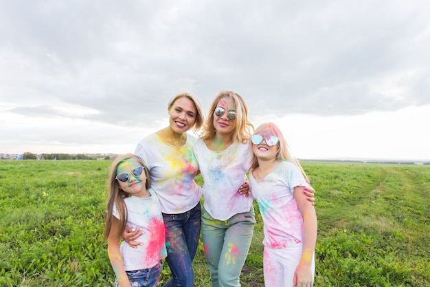 Family, festival of holi and holidays concept - portrait of mothers and daughters covered in paint