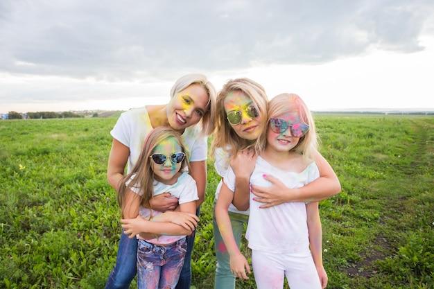 家族、ホーリー祭、休日のコンセプト-ペンキで覆われた母と娘の肖像画をクローズアップ。