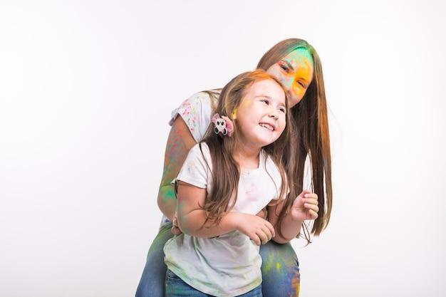 가족, holi 및 휴일 개념의 축제-여자와 작은 웃는 소녀는 화려한 덮여