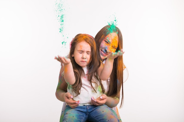 가족, holi 및 사람들 개념의 축제-여자와 작은 딸이 색으로 재미