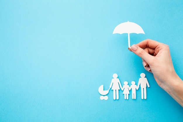 Family figure and hand holding umbrella shape