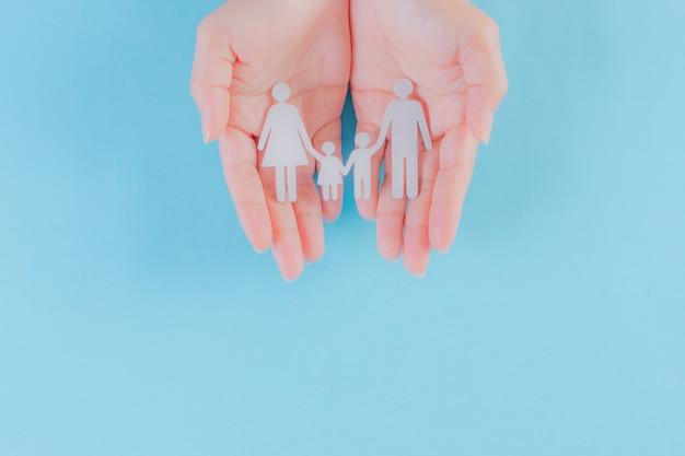 밝은 파란색 배경에 여자 손에 가족 그림. 세계 인구의 날 또는 보험 개념.