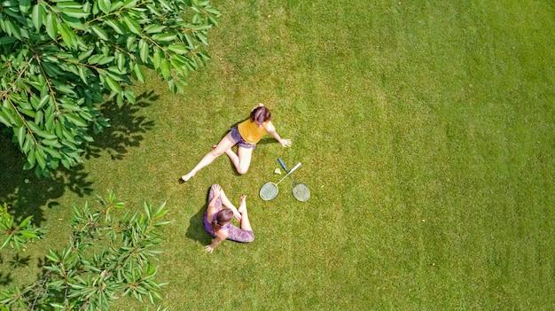 家族のフィットネスとスポーツアウトドア、アクティブな母と娘のティーンエイジャーが公園、空中のトップビューでバドミントンを演奏