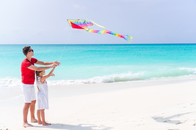 Family flying kite together at tropical white beach