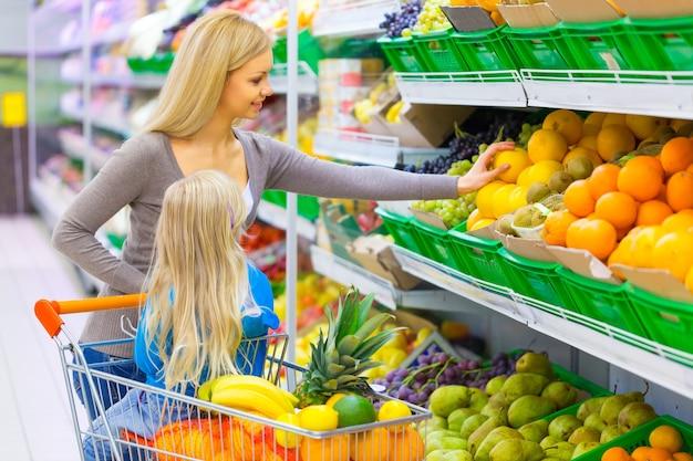 Семейные покупки еды. женщина мать и маленькая девочка дочь выбирают фрукты в супермаркете