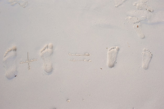 Family footprints on the white sand beach