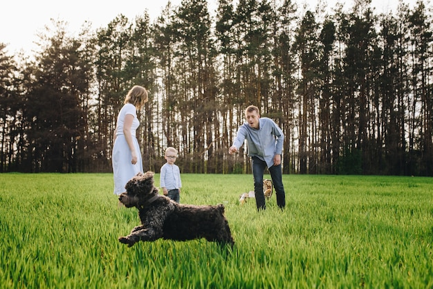 Family in the forest at a picnic. sit in a clearing, green grass. blue clothes. mom and dad play with their son, hug and smile. a child with glasses. time together picnic basket with food. pet - dog.