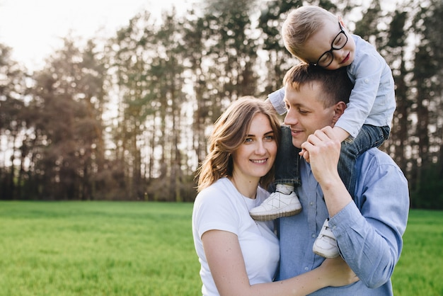 Family in the forest at a picnic. sit in a clearing, green grass. blue clothes. mom and dad play with their son, hug and smile. a child with glasses.