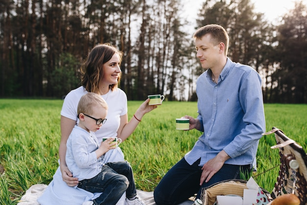Family in the forest at a picnic. sit in a clearing, green grass. blue clothes. mom and dad play with their son, hug and smile.
