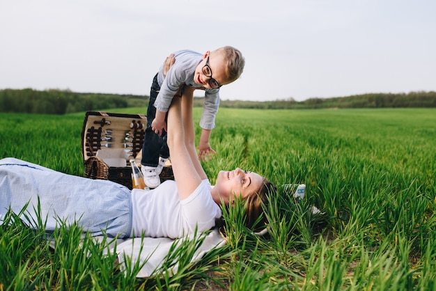 Family in the forest at a picnic. sit in a clearing, green grass. blue clothes. mom hugs son. a child with glasses. time together picnic basket with food. pet - dog.