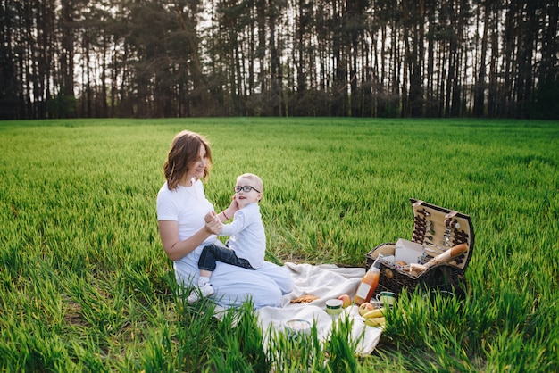Family in the forest at a picnic. sit in a clearing, green grass